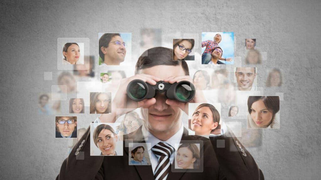 businessman looking for employees through binoculars