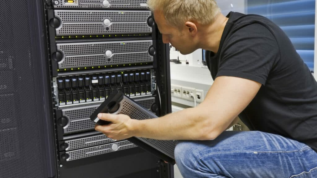 IT engineer working in a data center holding a disk cabinet