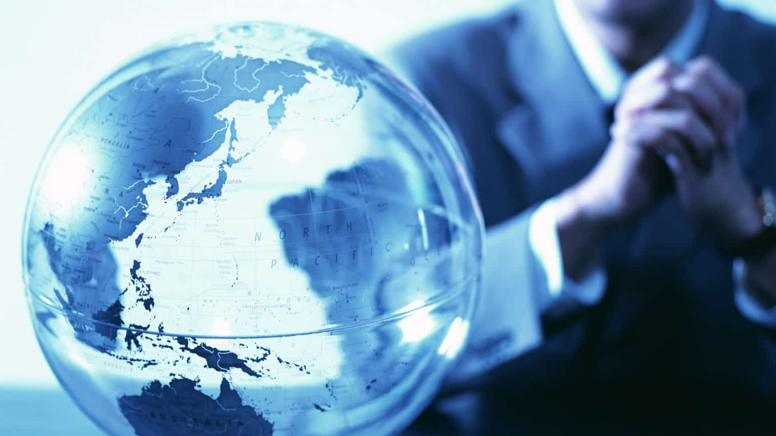 global business concept: man sitting next to a globe