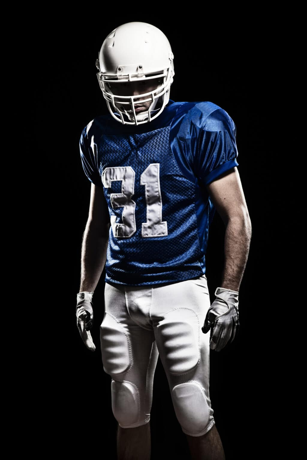 Football Player with number on a blue uniform. Studio shot.
