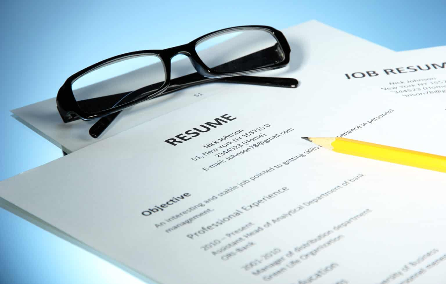 Closeup of resume with glasses and pencil on blue background