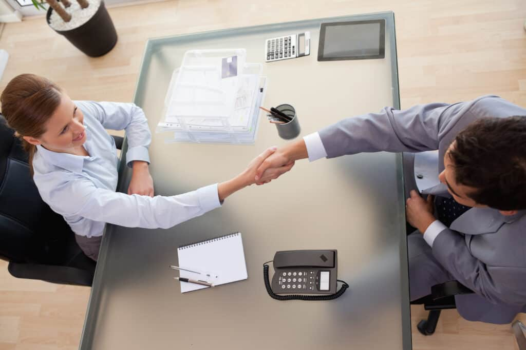 Above view of young consultant shaking hands with client
