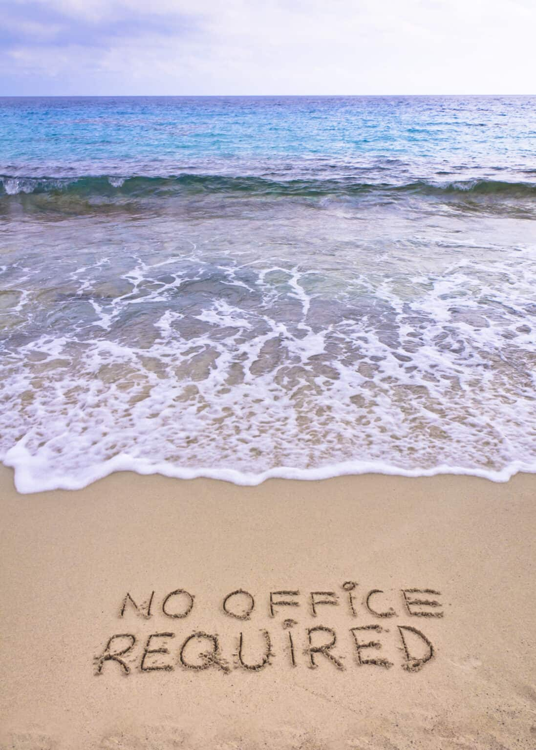 No office required written on sand, blue ocean water in background, freelancing concept