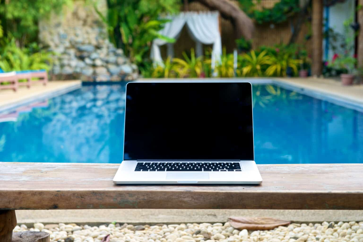 Laptop on a bench by the pool, working on vacation with mobility concept