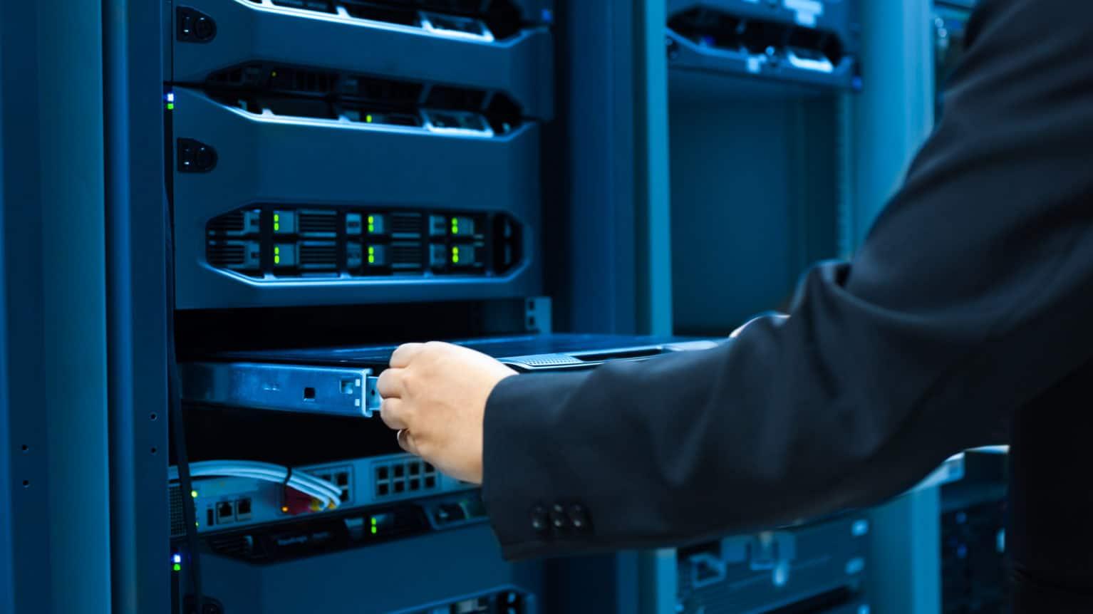 Man fixes server network in data center room