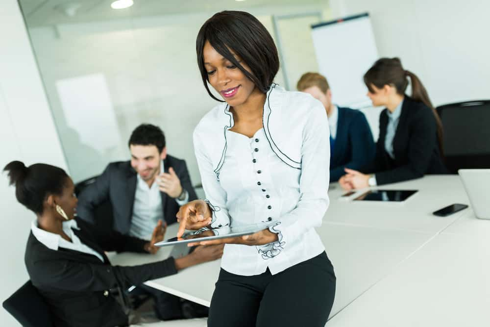 Beautiful, young, black, african businesswoman using a tablet at an office meeting