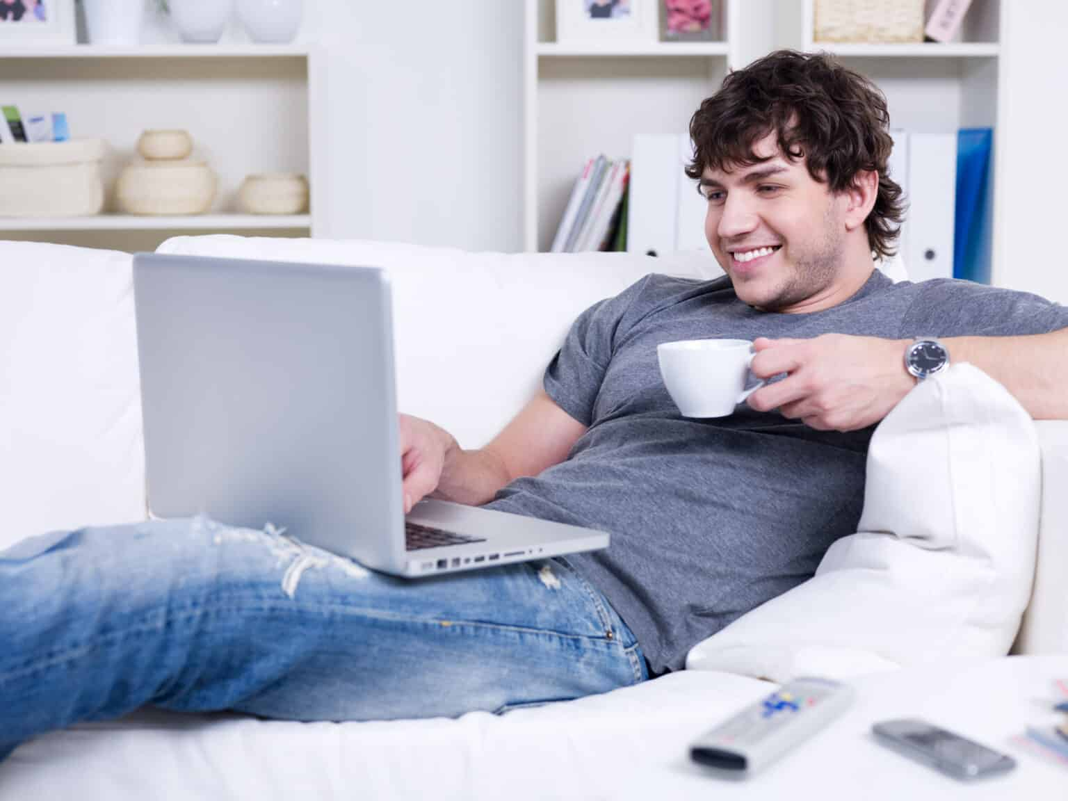 Handsome smiling young man with cup of coffee using laptop at home