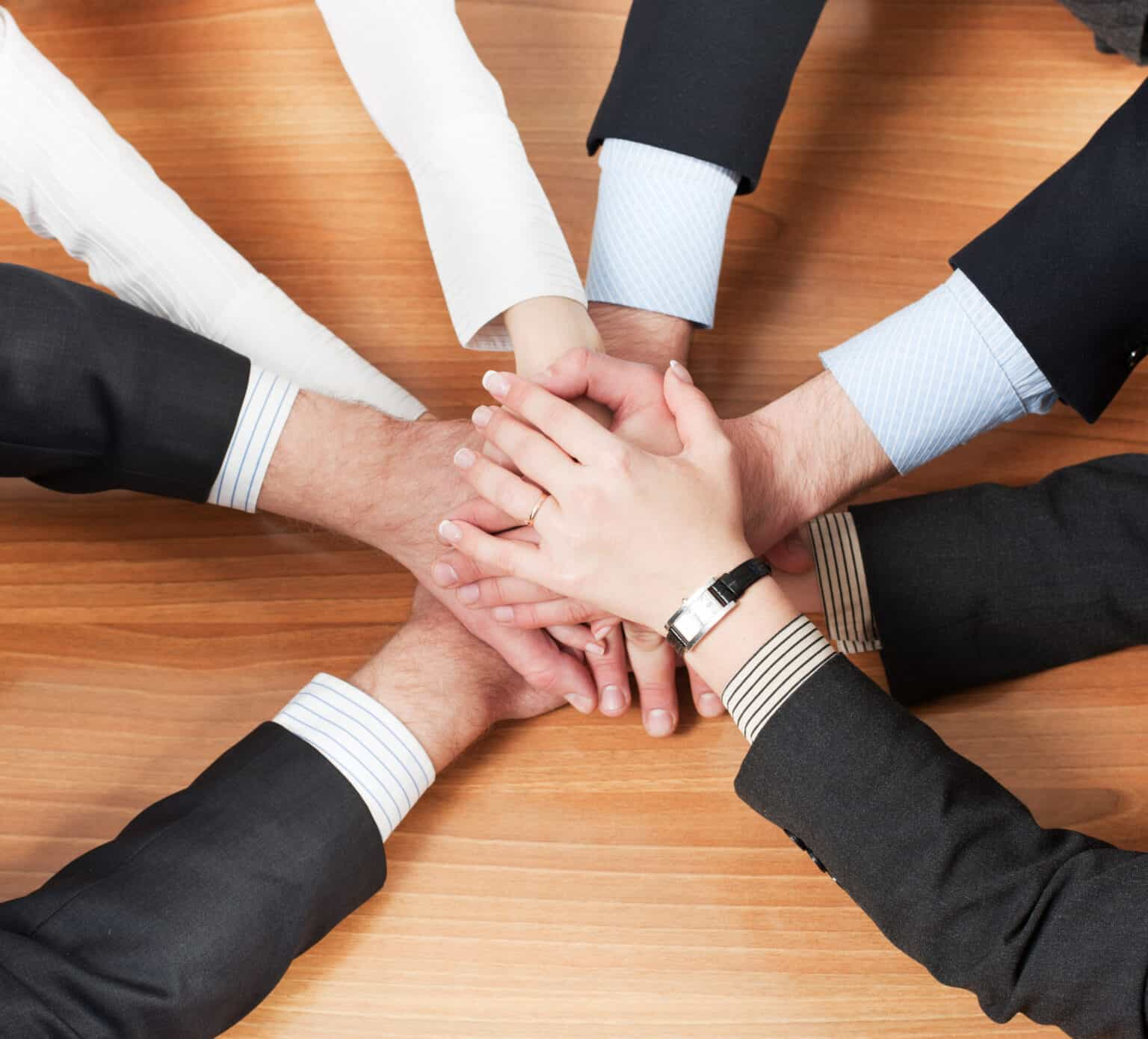 Office workers hold hands together on table