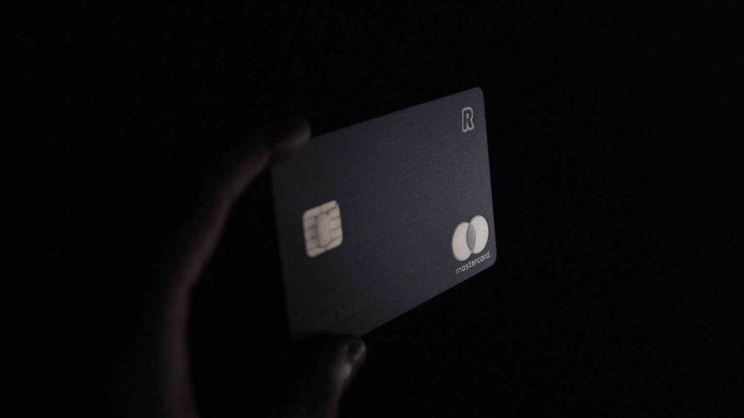 a hand holding a mastercard credit card