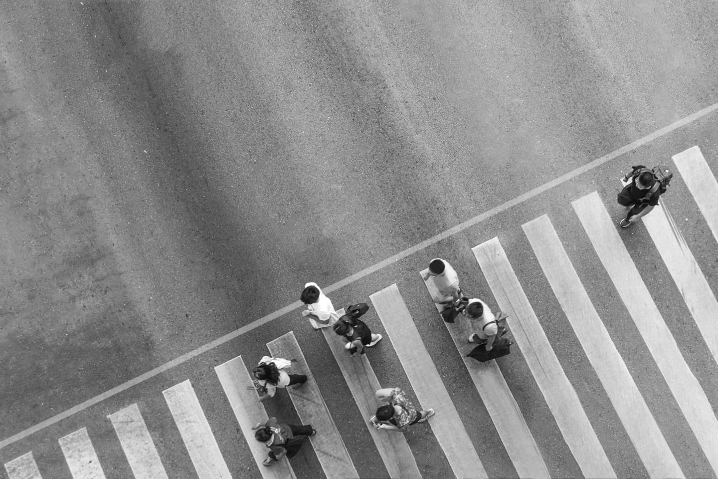 A city crowd moves along a pedestrian crosswalk on a busy road (aerial, top view photo)