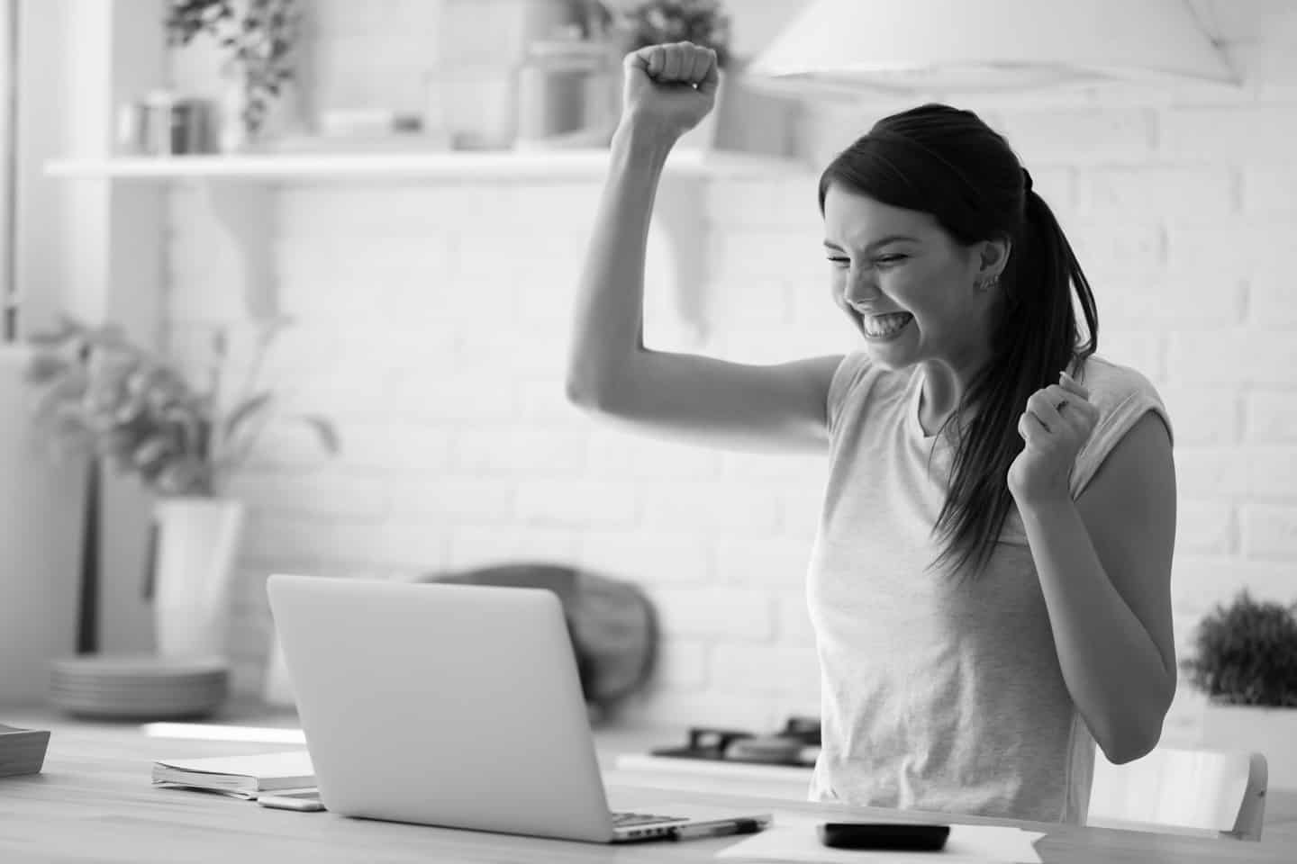 Woman with laptop and calculator excited about finally paying down her mortgage. Young lady super happy about refund approval email. Smiling millennial woman celebrating successful online investment